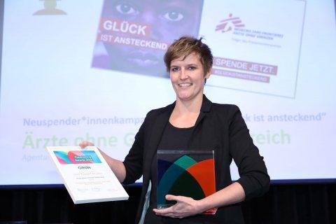 Andrea Buhl-Aigner, Leitung Digital Communications Unit bei Ärzte ohne Grenzen Österreich, mit der Urkunde und dem Pokal des GRÜN Fundraising Awards