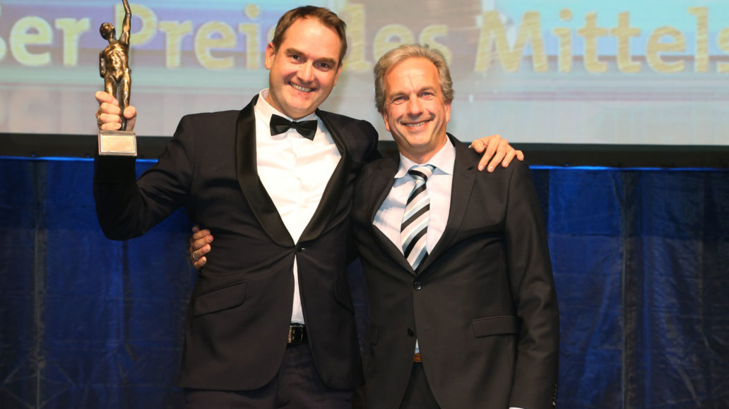 "Dr. Oliver Grün, Founder, board member and CEO of GRÜN Software AG, and COO Dirk Hönscheid with the statue of the winner of the ""Grand Prize for SMEs"". Source: Oskar Patzelt Foundation"